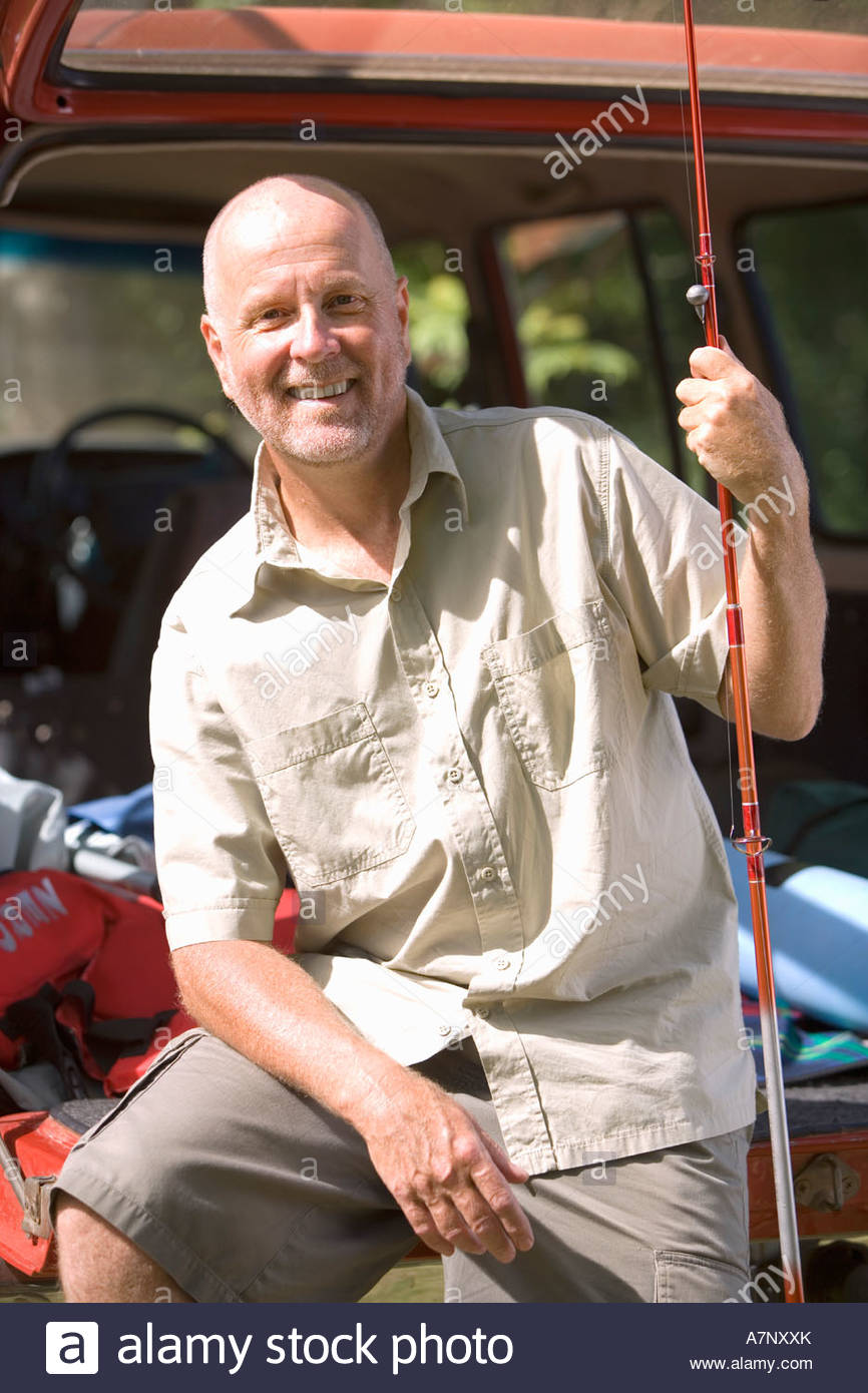 Senior man sitting in boot of parked SUV holding fishing rod smiling portrait - Stock Image