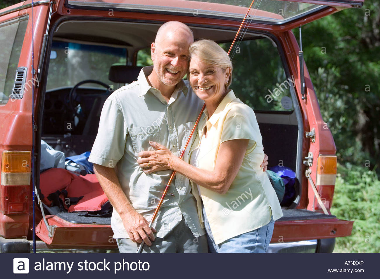 Senior couple standing beside parked SUV arms around each other man with fishing rod smiling portrait - Stock Image
