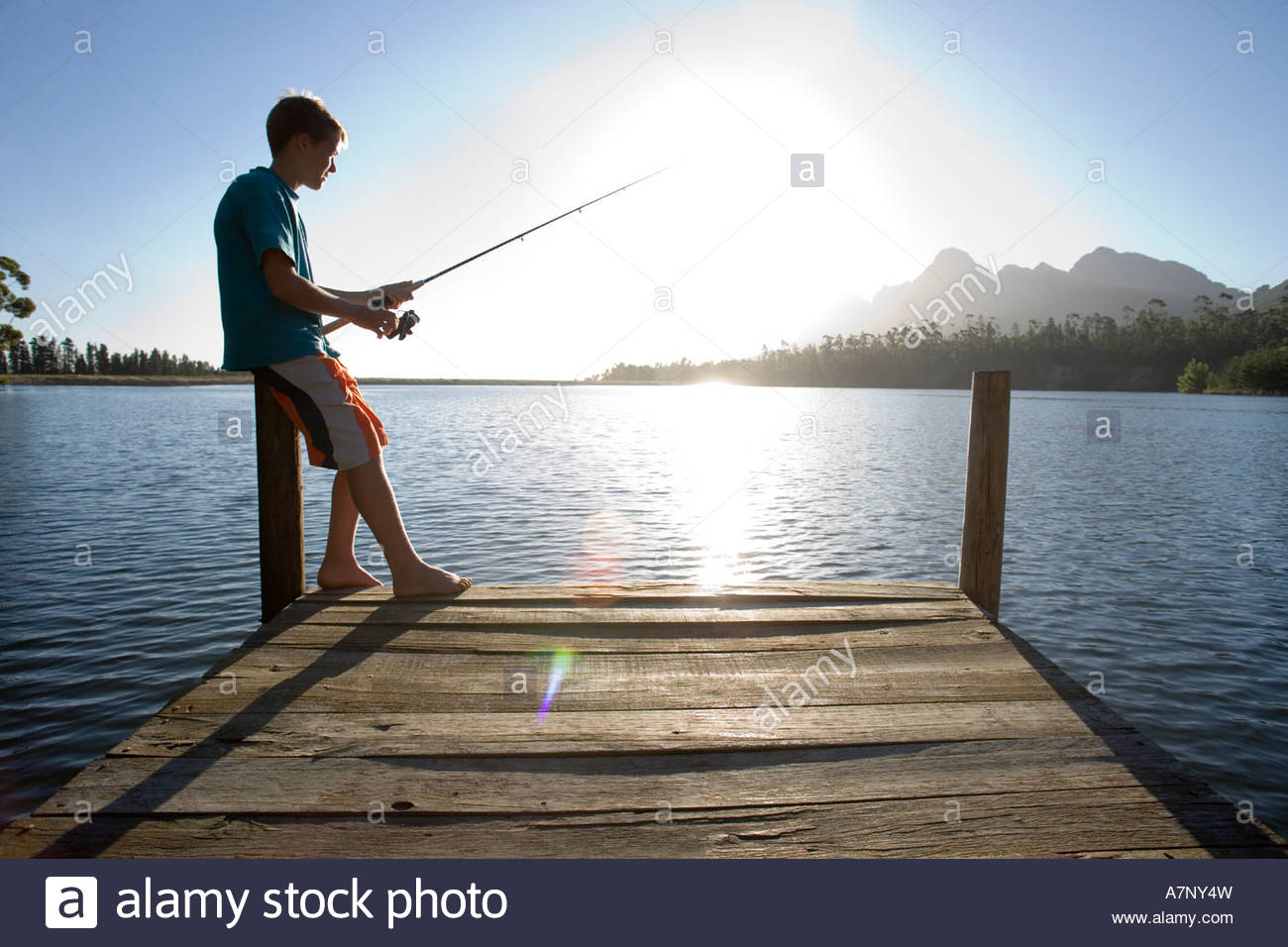 Solitary teenage boy 12 14 standing at edge of jetty fishing in lake on sunny day side view lens flare backlit - Stock Image