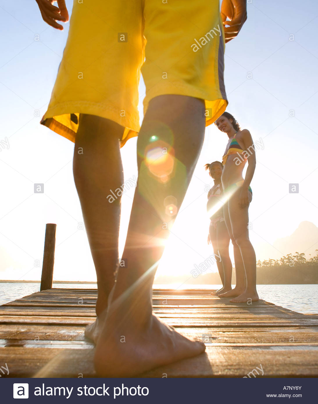 Family standing on jetty man in yellow swimming shorts preparing to jump into lake low section rear view surface - Stock Image