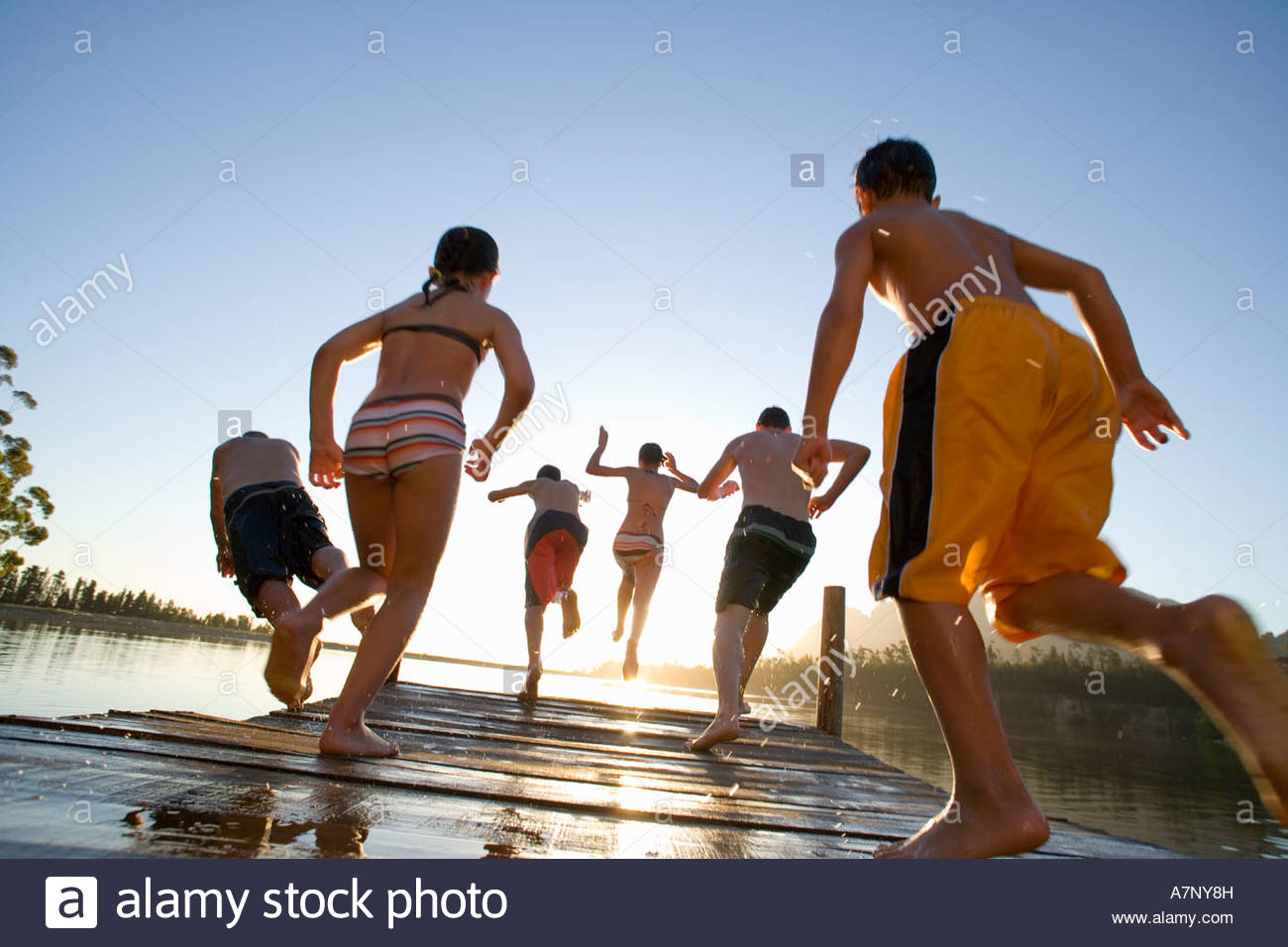 Six family members in swimwear jumping from jetty into lake at sunset rear view lens flare backlit surface level - Stock Image