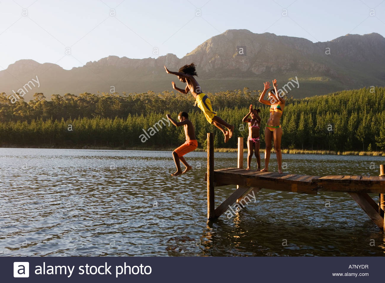Family in swimwear standing on jetty father and son 8 10 jumping into lake side view - Stock Image