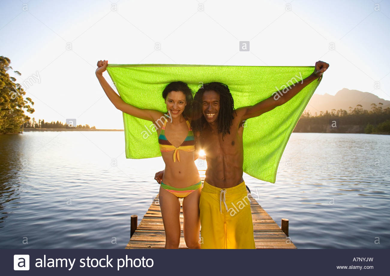 Couple standing on lake jetty arms around each other holding aloft green towel smiling front view portrait - Stock Image