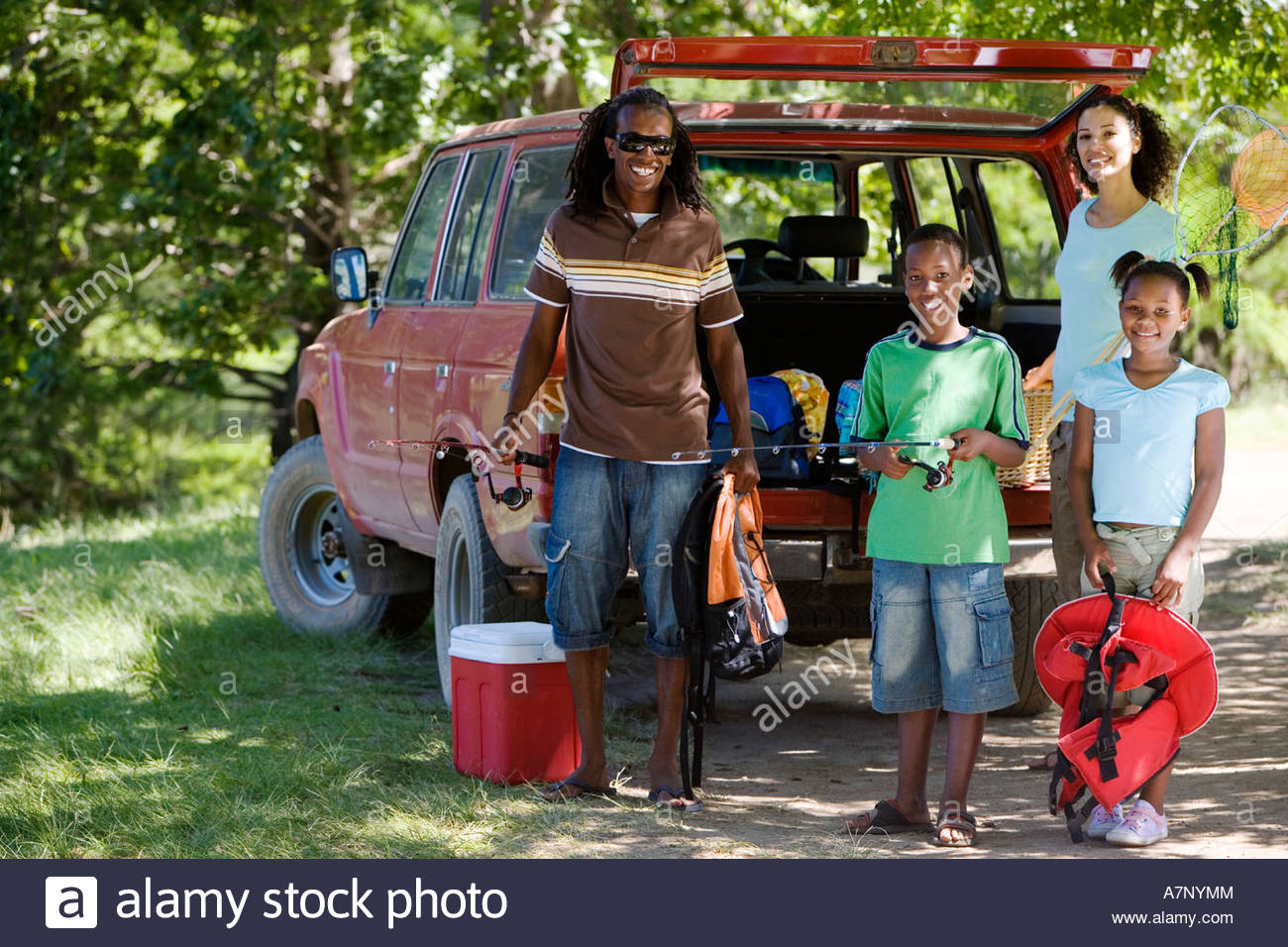 Family unloading parked SUV on camping trip girl 7 9 holding life jacket smiling portrait - Stock Image