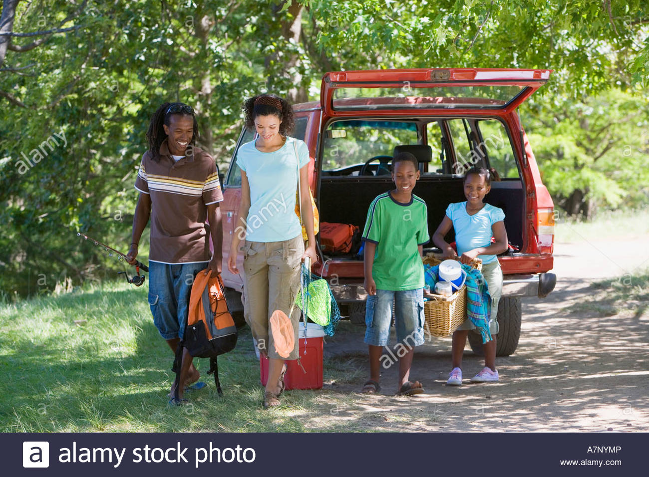 Family unloading parked SUV on camping trip children 7 10 carrying picnic hamper smiling portrait - Stock Image