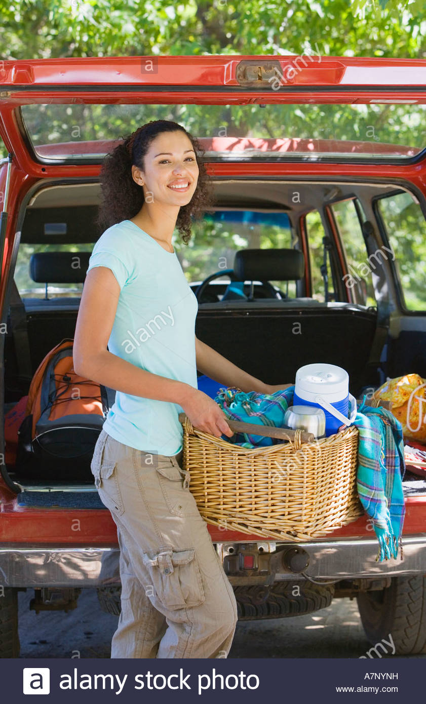 woman unloading parked suv on family camping trip carrying picnic