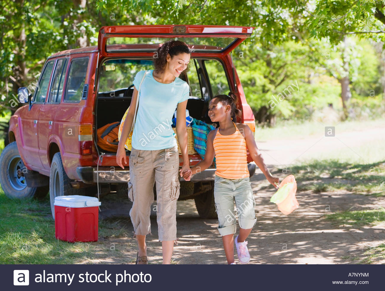 Mother and son 8 10 unloading parked SUV on camping trip holding hands smiling - Stock Image
