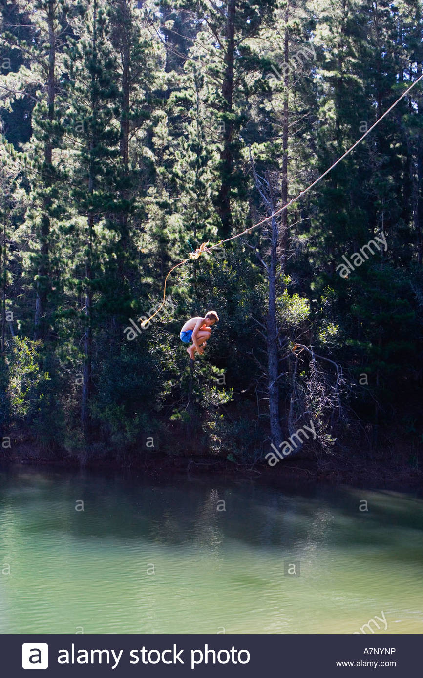 Boy 8 10 in swimming shorts letting go of rope swing above lake hugging knees side view - Stock Image