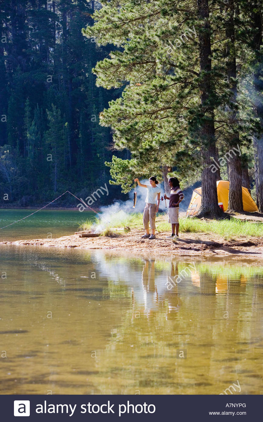 Couple in mid distance fishing near lakeside campfire woman holding aloft fish side view - Stock Image
