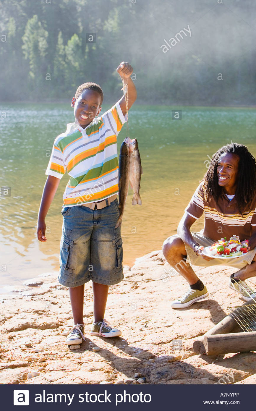 Proud boy 8 10 holding aloft fish on lakeside camping trip father holding plate of food smiling portrait Stock Photo