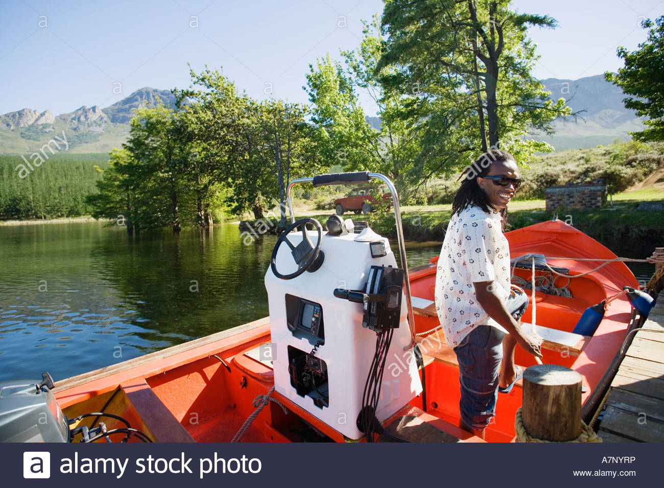 Man standing in motorboat beside lake jetty leaning on rope tied to mooring post side view smiling portrait Stock Photo
