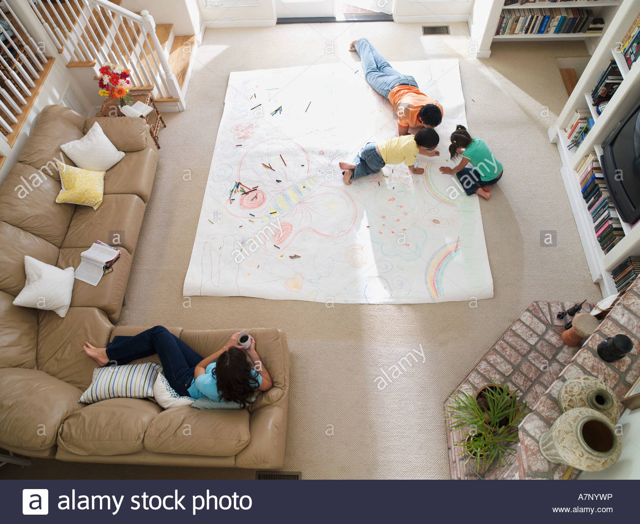 Family drawing on large piece of paper laid out on living room floor overhead view - Stock Image