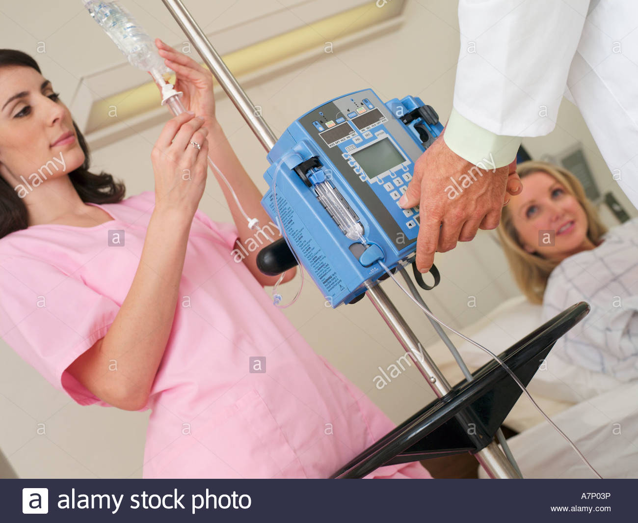 Nurse attending to female patient's IV drip in hospital ward, doctor operating control (tilt) - Stock Image