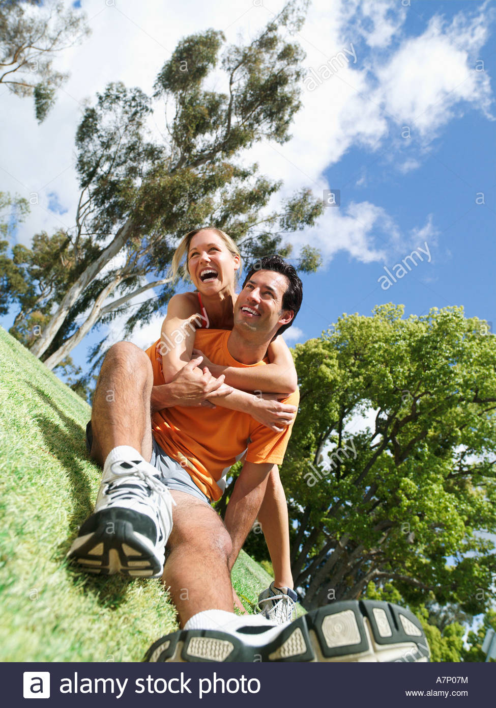 Couple taking break from jogging in park man sitting on grass woman embracing man laughing tilt surface level - Stock Image