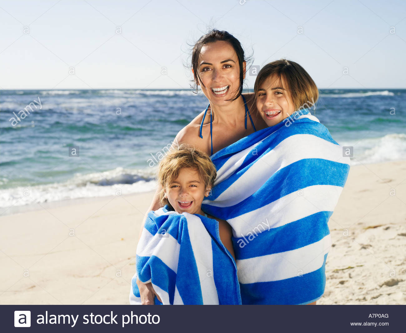 Mother drying two daughters 5 12 with stripy blue towel on sandy beach smiling portrait - Stock Image