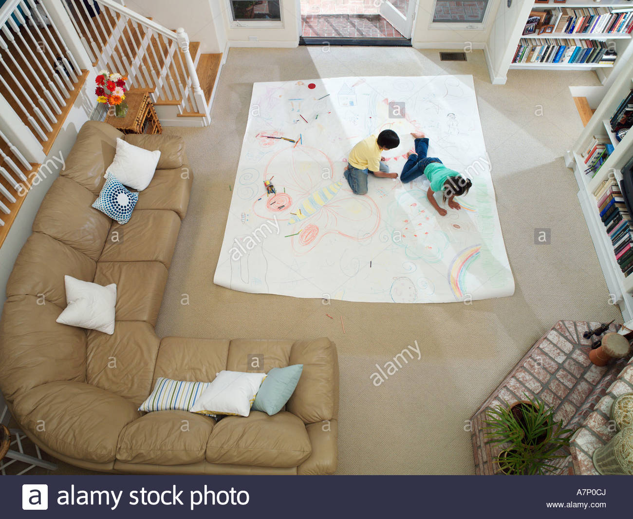 Boy and girl 7 10 drawing on large piece of paper laid out on living room floor overhead view - Stock Image