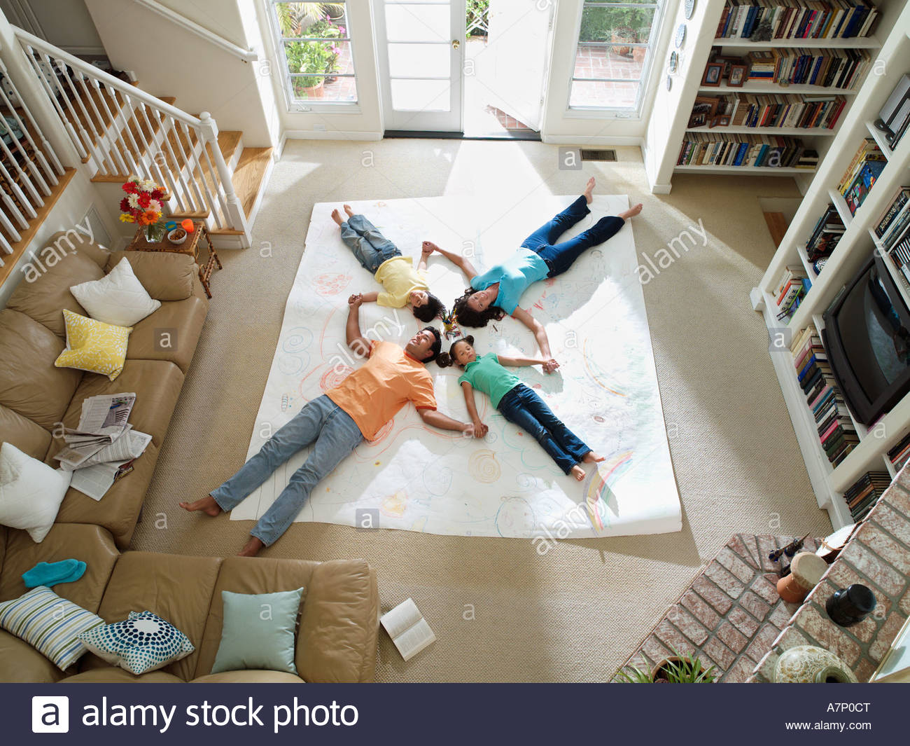 Family lying together on large piece of paper laid out on living room floor overhead view - Stock Image