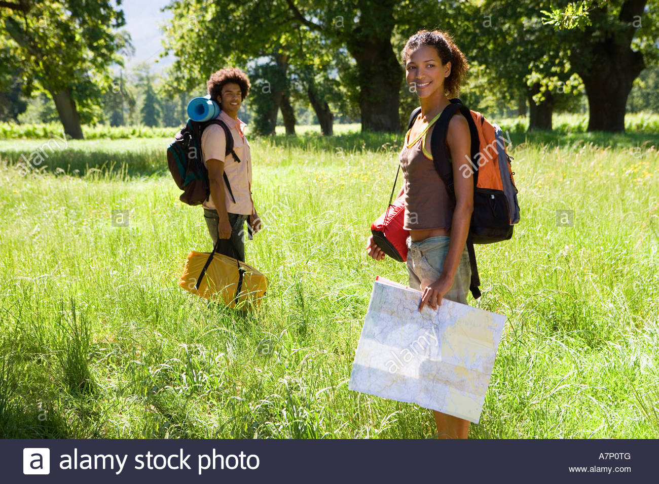 Young couple with rucksacks standing in woodland clearing departing on hiking trip woman holding map smiling portrait - Stock Image