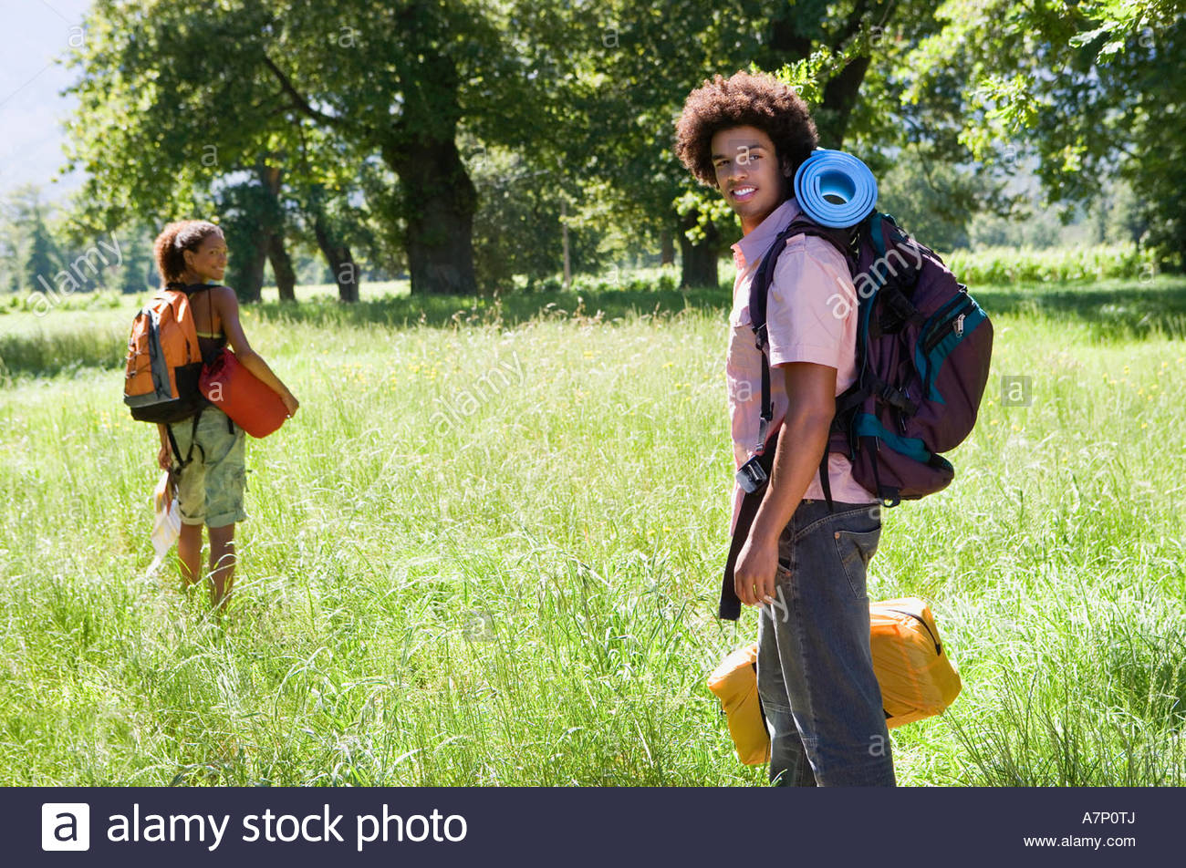 Young couple with rucksacks standing in woodland clearing departing on hiking trip side view smiling portrait - Stock Image