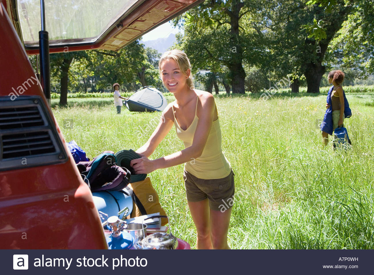 Young woman unloading parked SUV in woodland clearing on camping trip side view smiling portrait - Stock Image