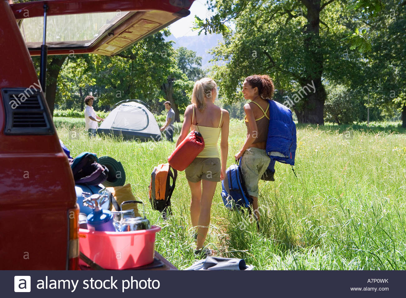 Two young women unloading parked SUV in woodland clearing on camping trip rear view smiling - Stock Image