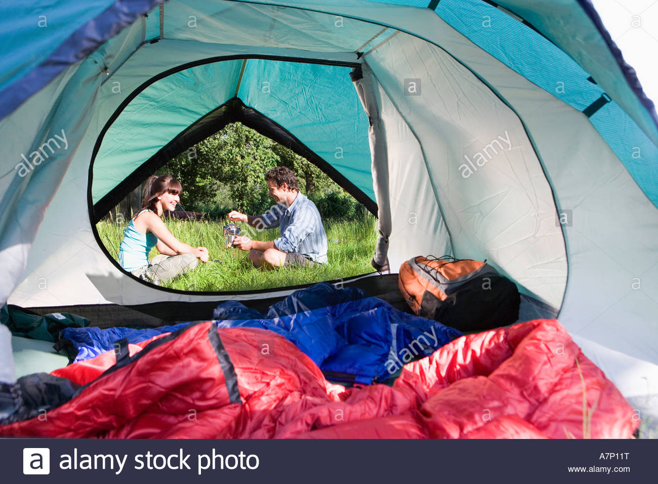 Tent interior view of couple sitting outside on grass pouring water from hot kettle - Stock Image