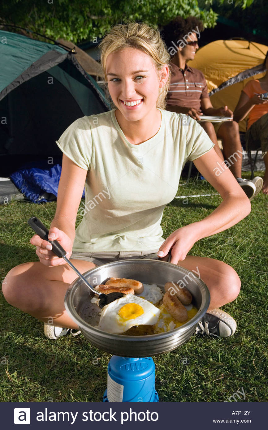 Young adults eating fried breakfast beside tents focus on woman with spatula cooking on camping stove portrait - Stock Image