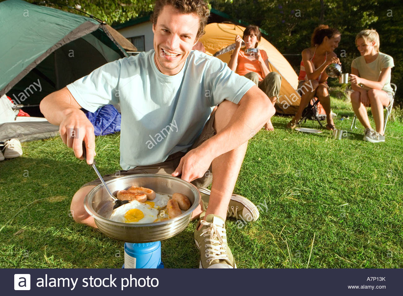 Young adults eating fried breakfast beside tents focus on man with spatula cooking on camping stove portrait tilt Stock Photo