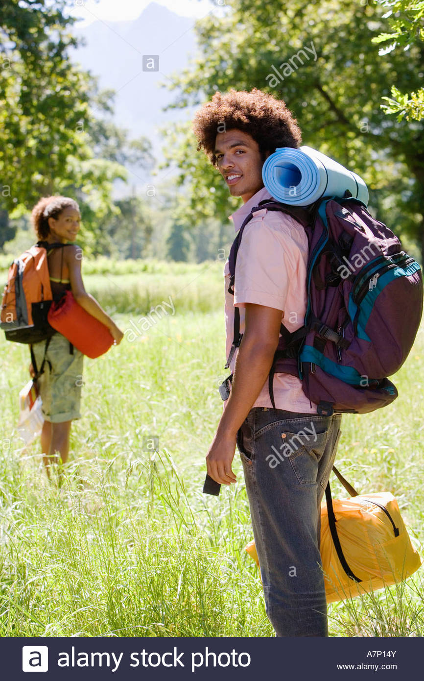 Young couple with rucksacks standing in woodland clearing departing on hiking trip man carrying sleeping bag smiling - Stock Image