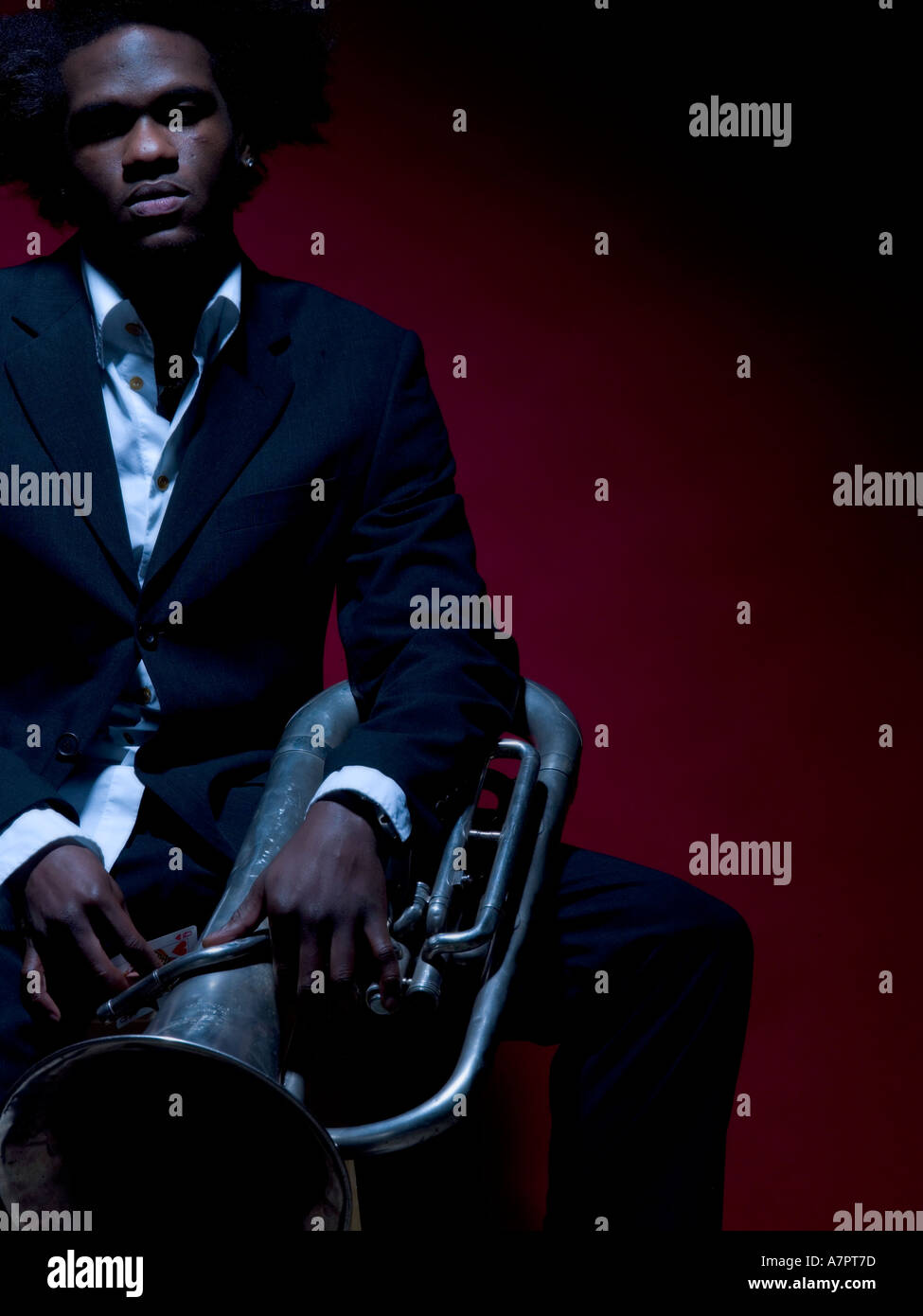 20 s Afro Caribbean male sat hoding a fench horn on lap - Stock Image