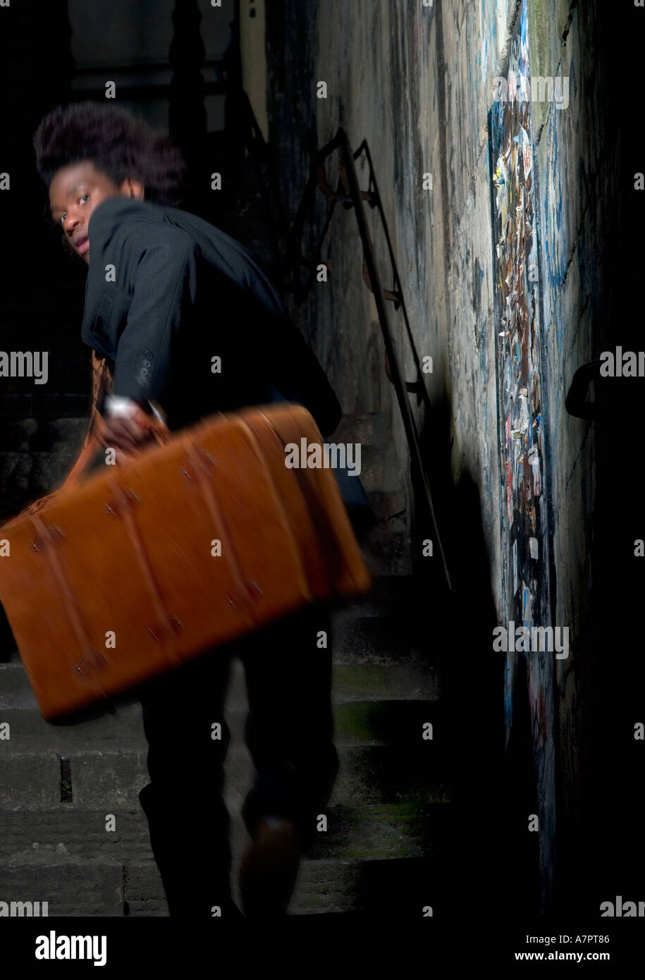 20 s Afro Caribbean male running up a flight of stairs holding a brown leather suitcase - Stock Image
