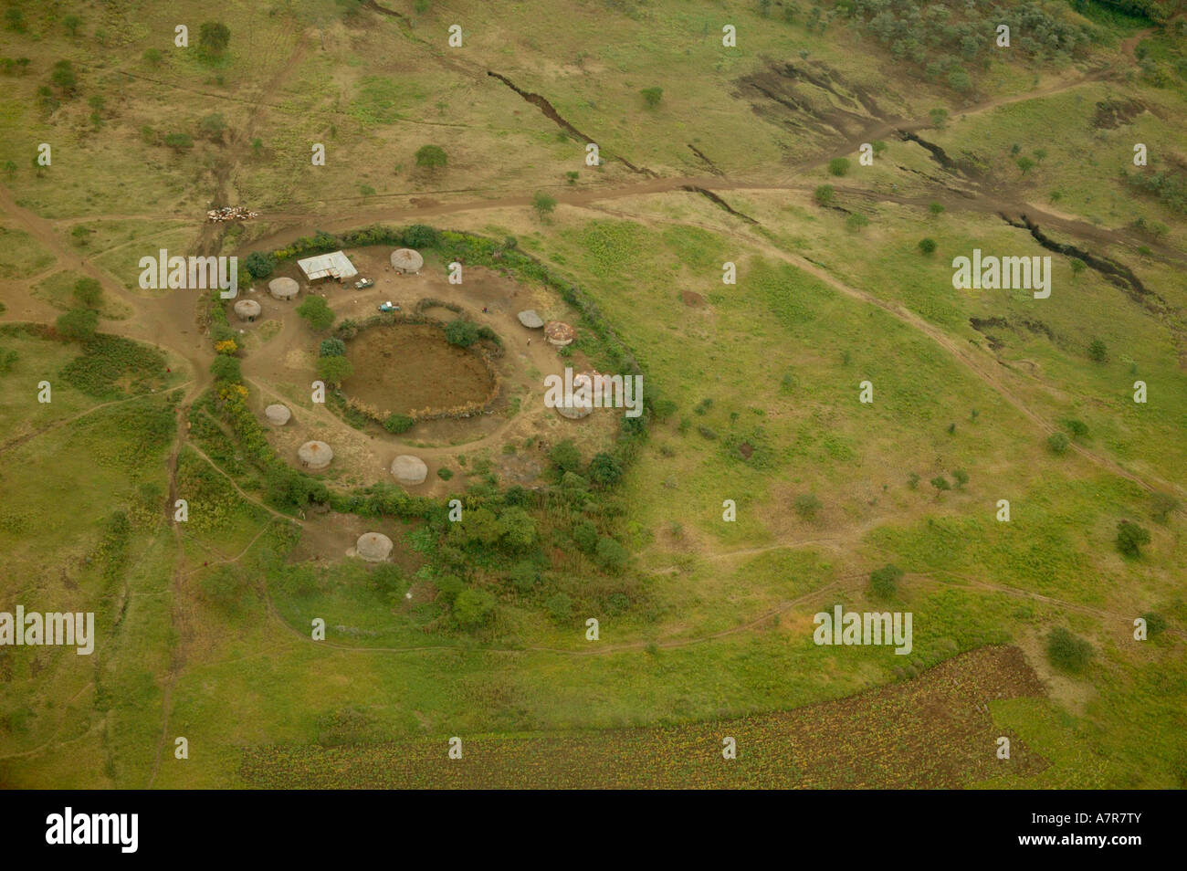 An aerial view of a traditional Masaai homestead with a number of huts around the periphery of a central cattle - Stock Image