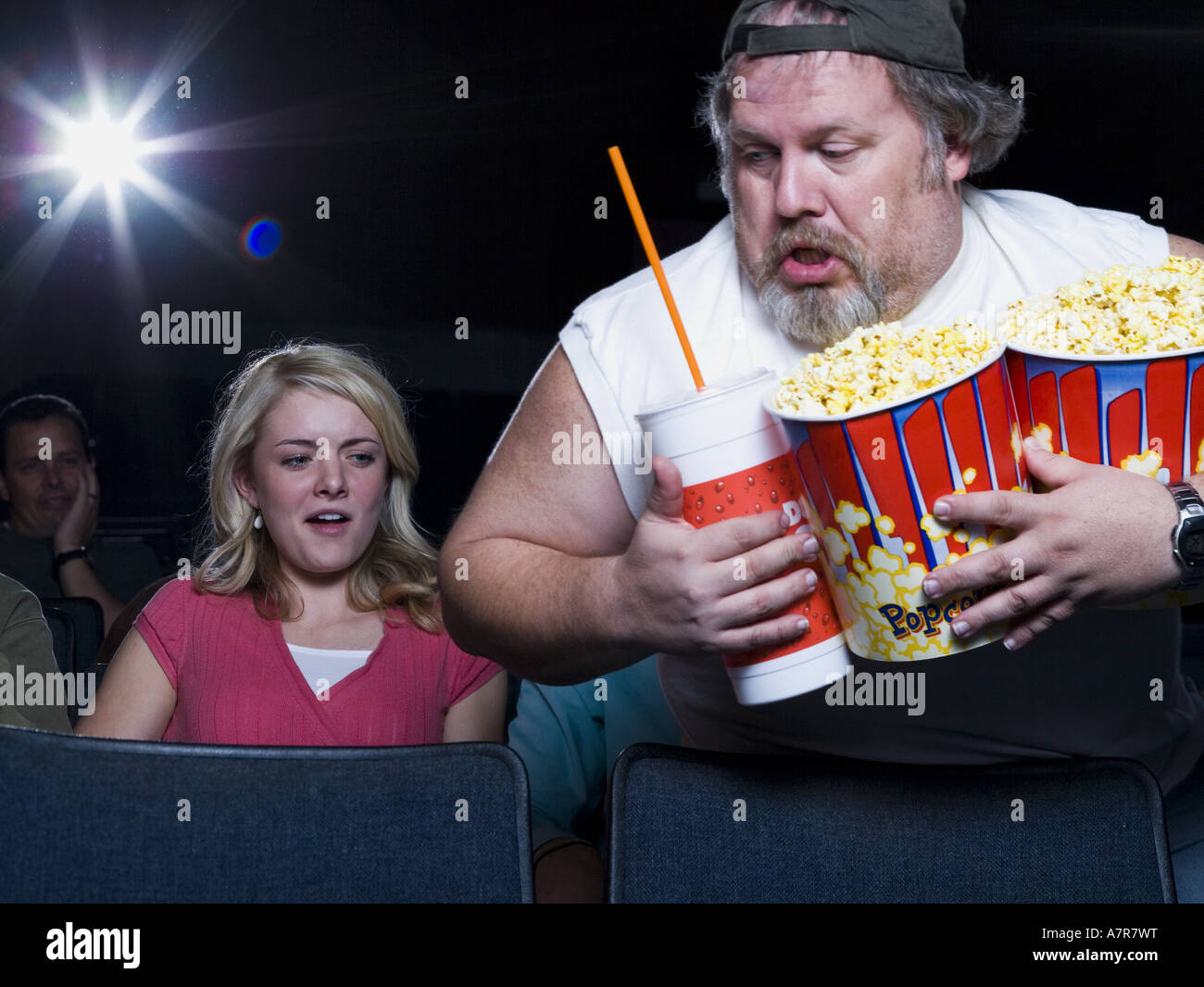 large man with buckets of popcorn and drink at movie theater stock