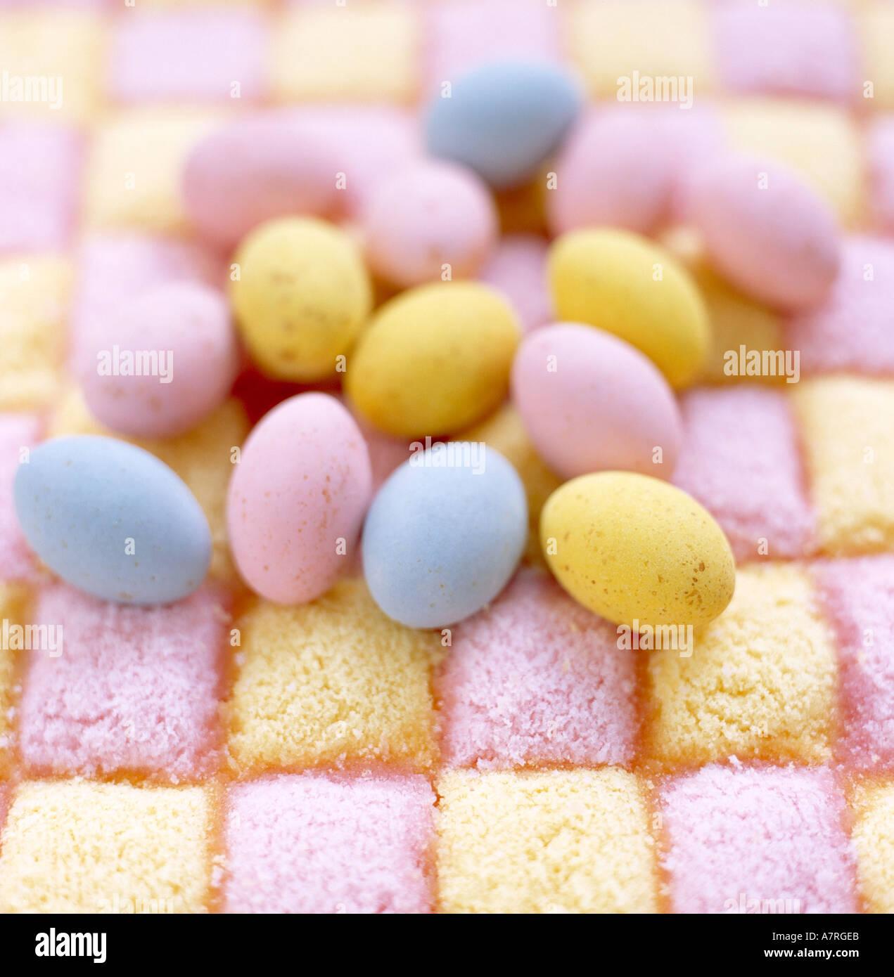 close up of pastel coloured coated chocolate mini eggs on Battenburg cake background - Stock Image