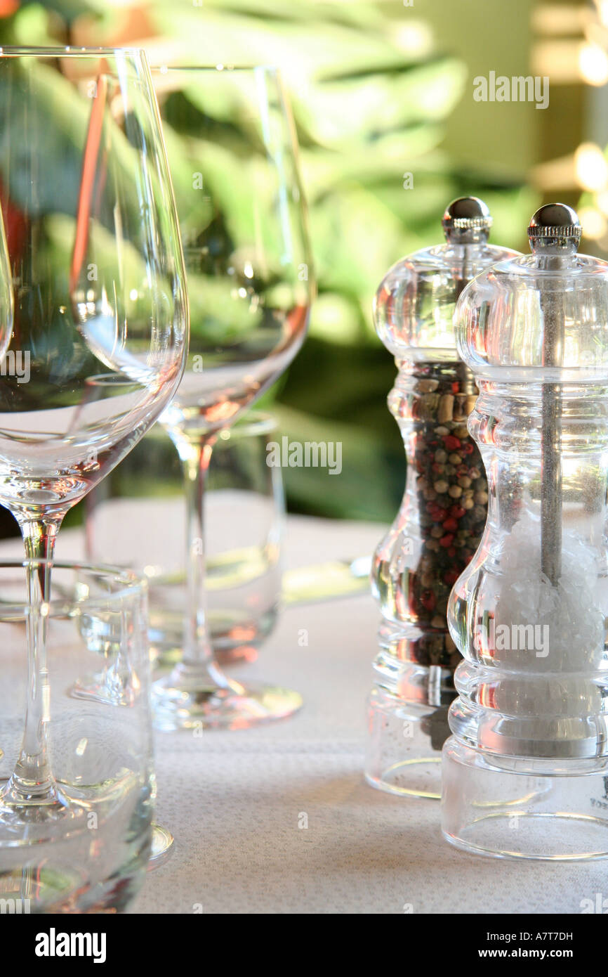 Salt and pepper shaker with stem glass on table - Stock Image