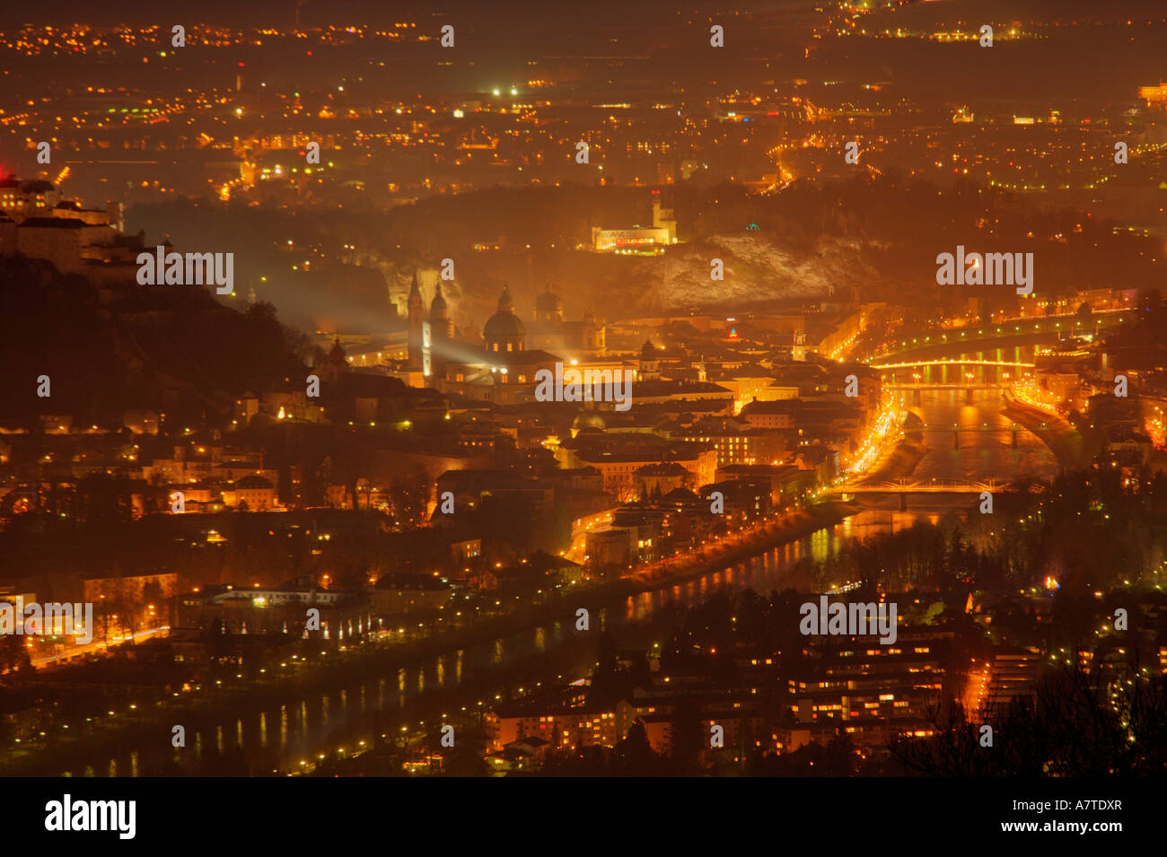 Aerial view of cityscape lit up at night, Salzach River, Salzburg, Austria Stock Photo