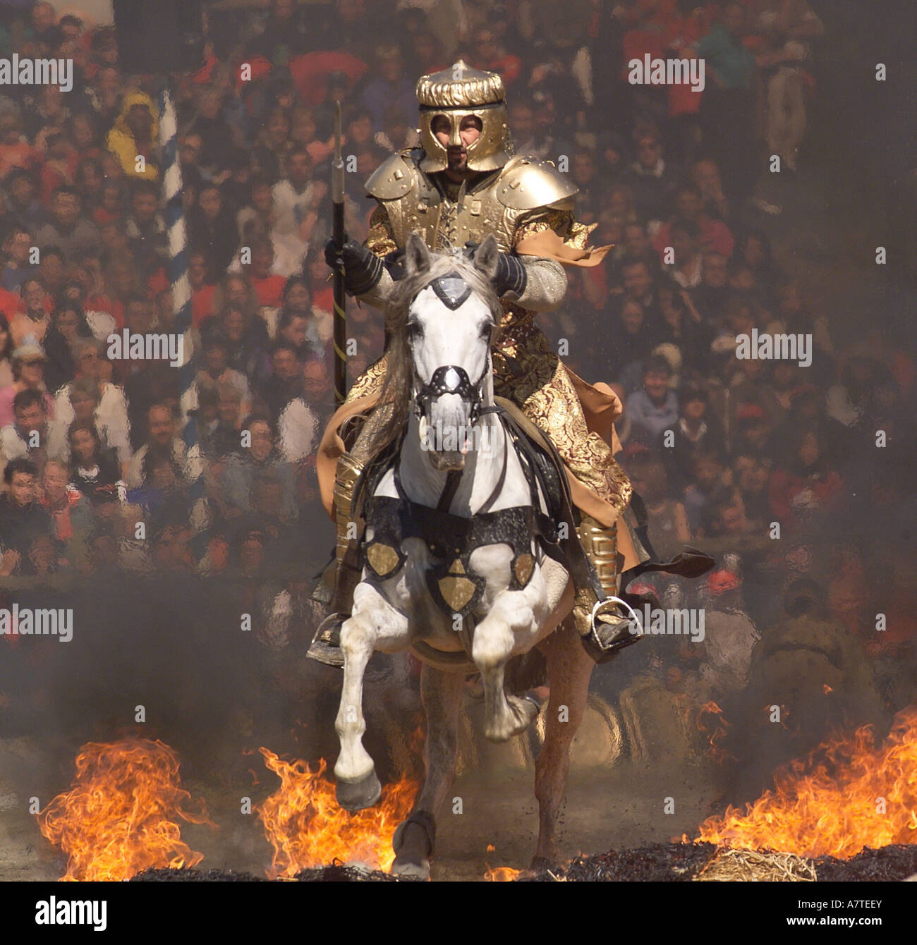 Knight in armour suit riding horse through fire, Bavaria, Germany - Stock Image