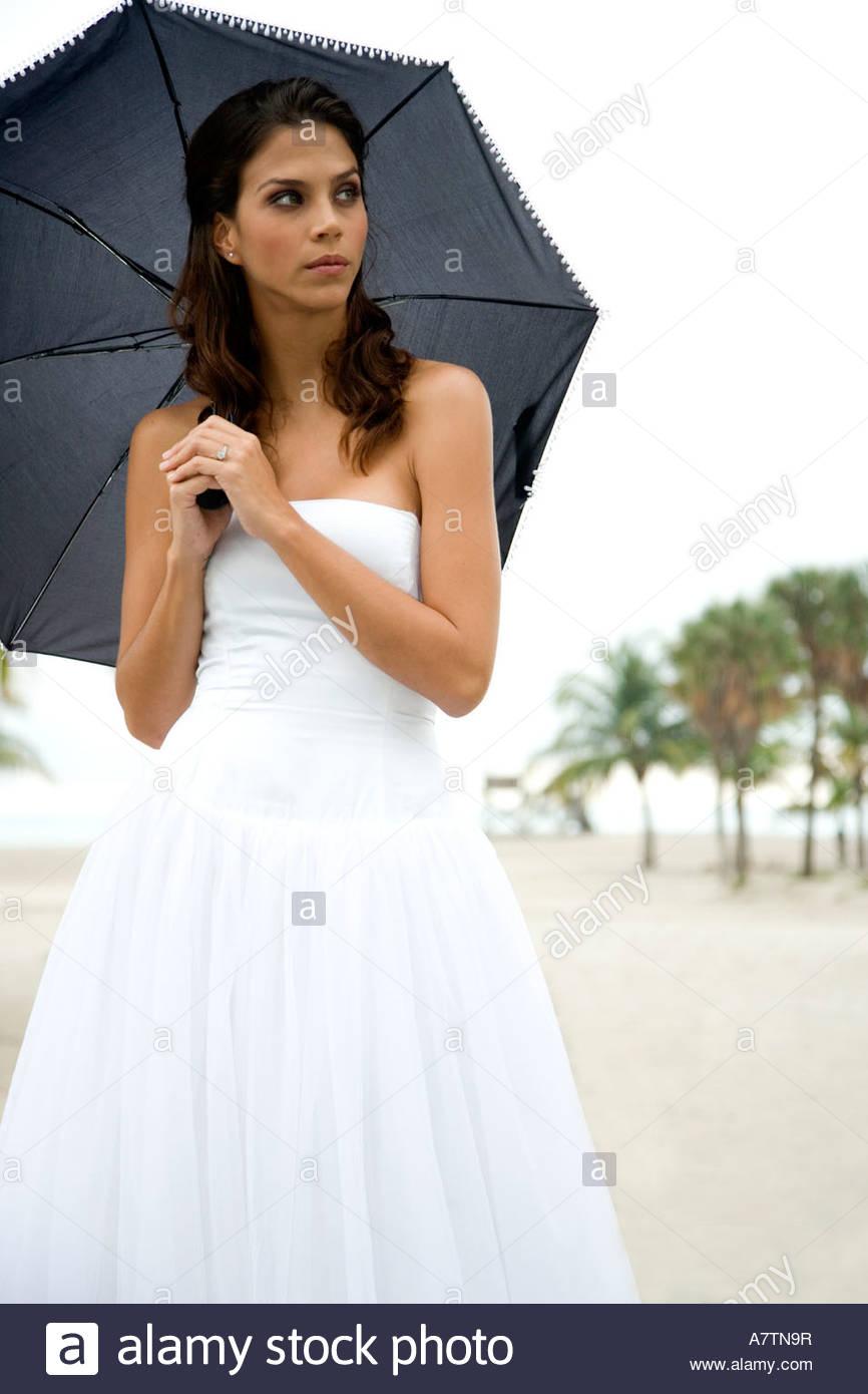 A bride standing under an umbrella - Stock Image