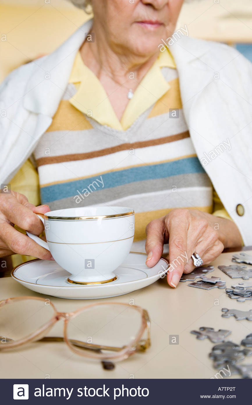 An elderly woman completing a jigsaw - Stock Image