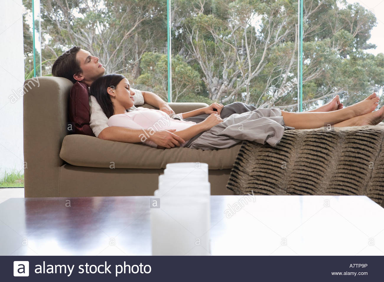 A young couple laying on a sofa - Stock Image