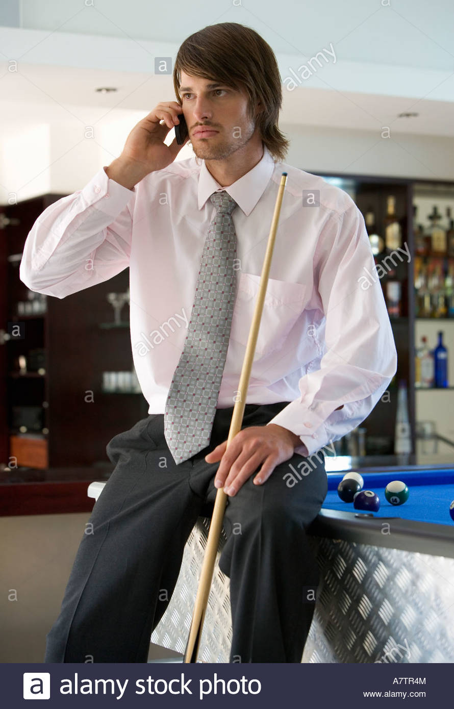 A businessman playing pool in a bar - Stock Image