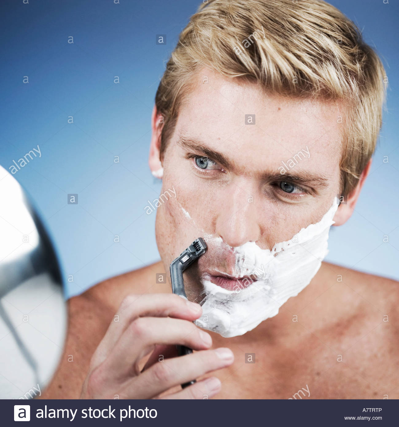 A young man shaving - Stock Image