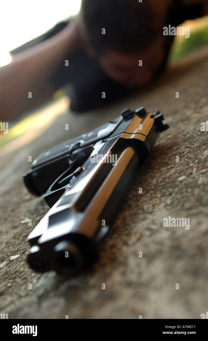 a man being arrested in possession of a weapon - Stock Image