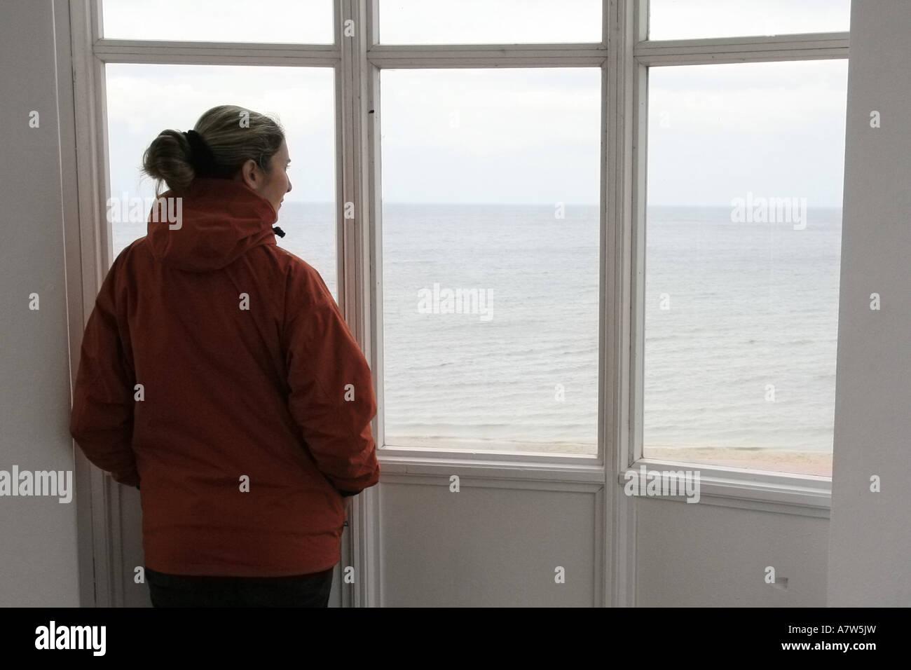 woman looking through windows over Baltic Sea, Germany, Ruegen, Binz - Stock Image