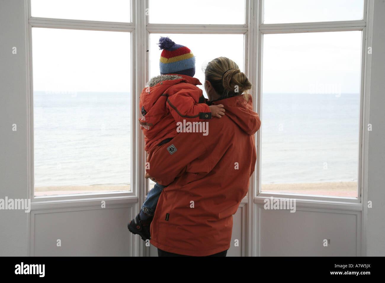 woman and child looking through windows over Baltic Sea, Germany, Ruegen, Binz - Stock Image