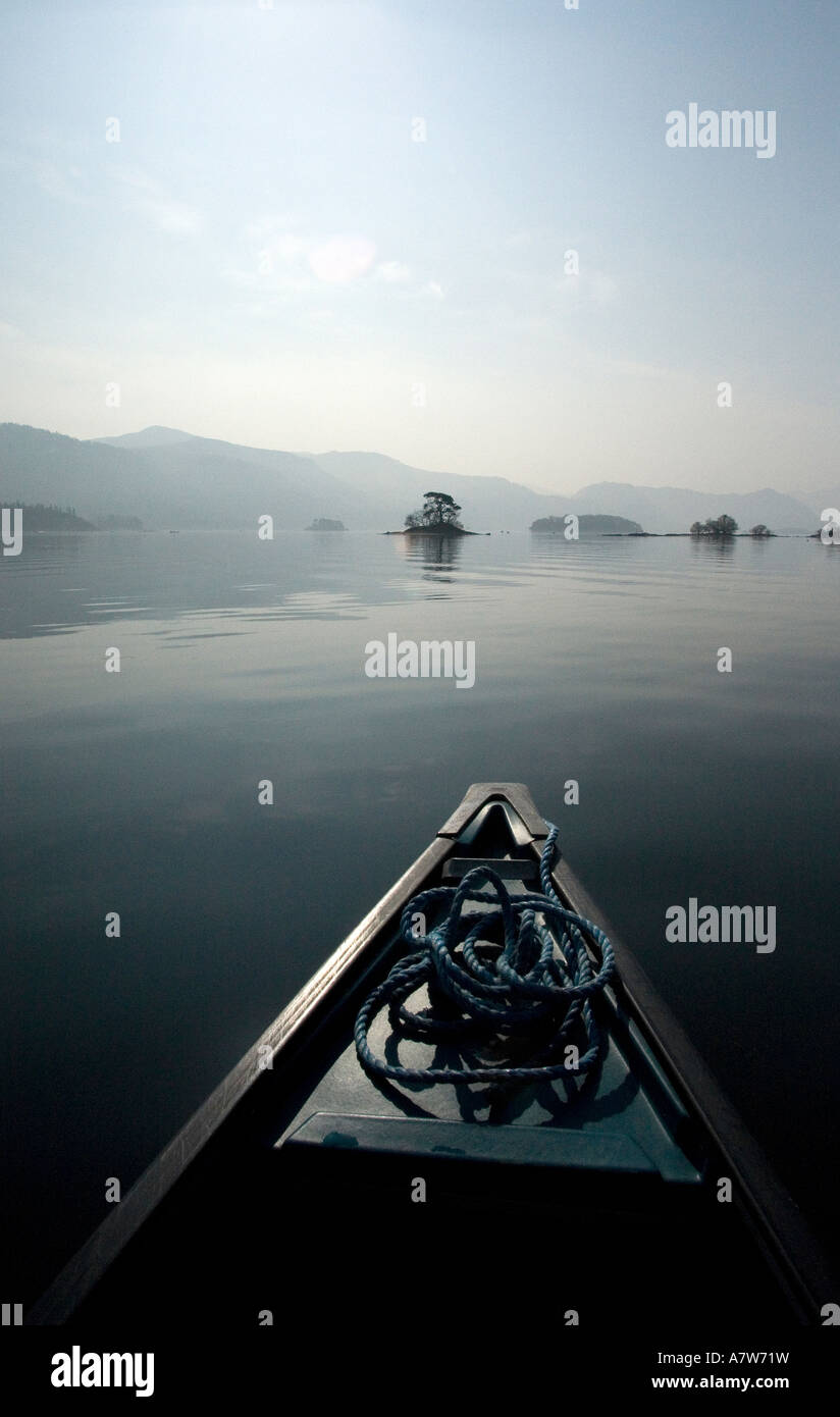 Cutting free. Escapism in a canoe, early on a misty, still morning. Dream like quality to sailing to the ends of - Stock Image