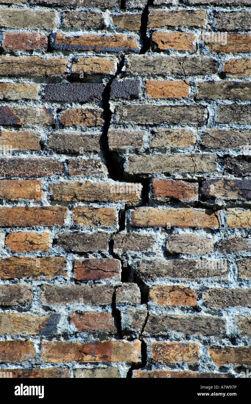 an old brick wall with a large crack in it - Stock Image