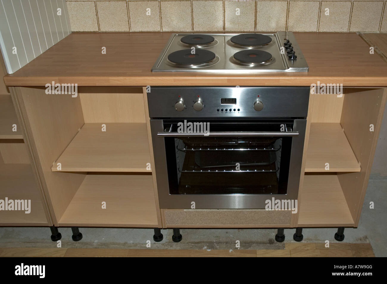 a new cooker being fitted into a new kitchen - Stock Image