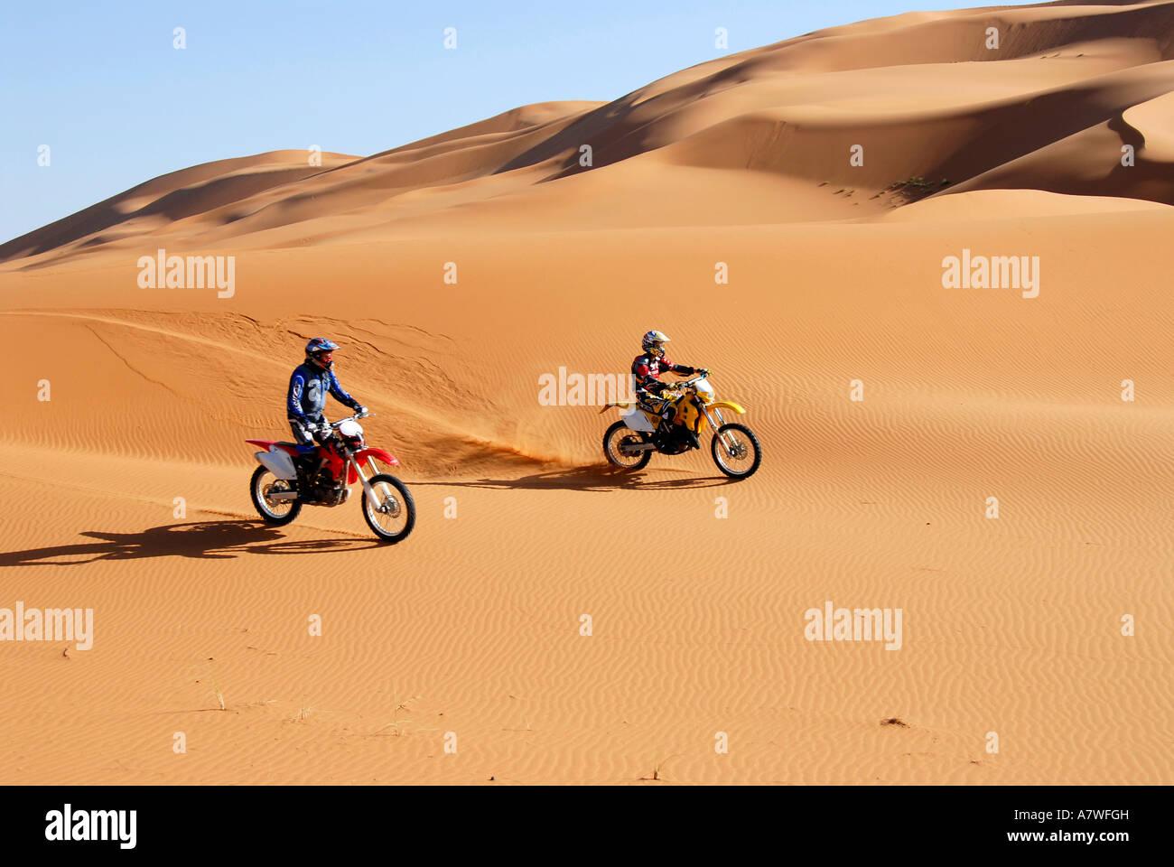 Two Moto Cross riders in sand dunes Erg Chebbi Merzouga Morocco - Stock Image