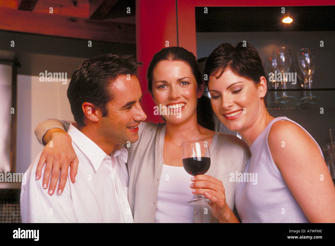 portrait of a group of two young women and one man standing in the kitchen drinking wine - Stock Image